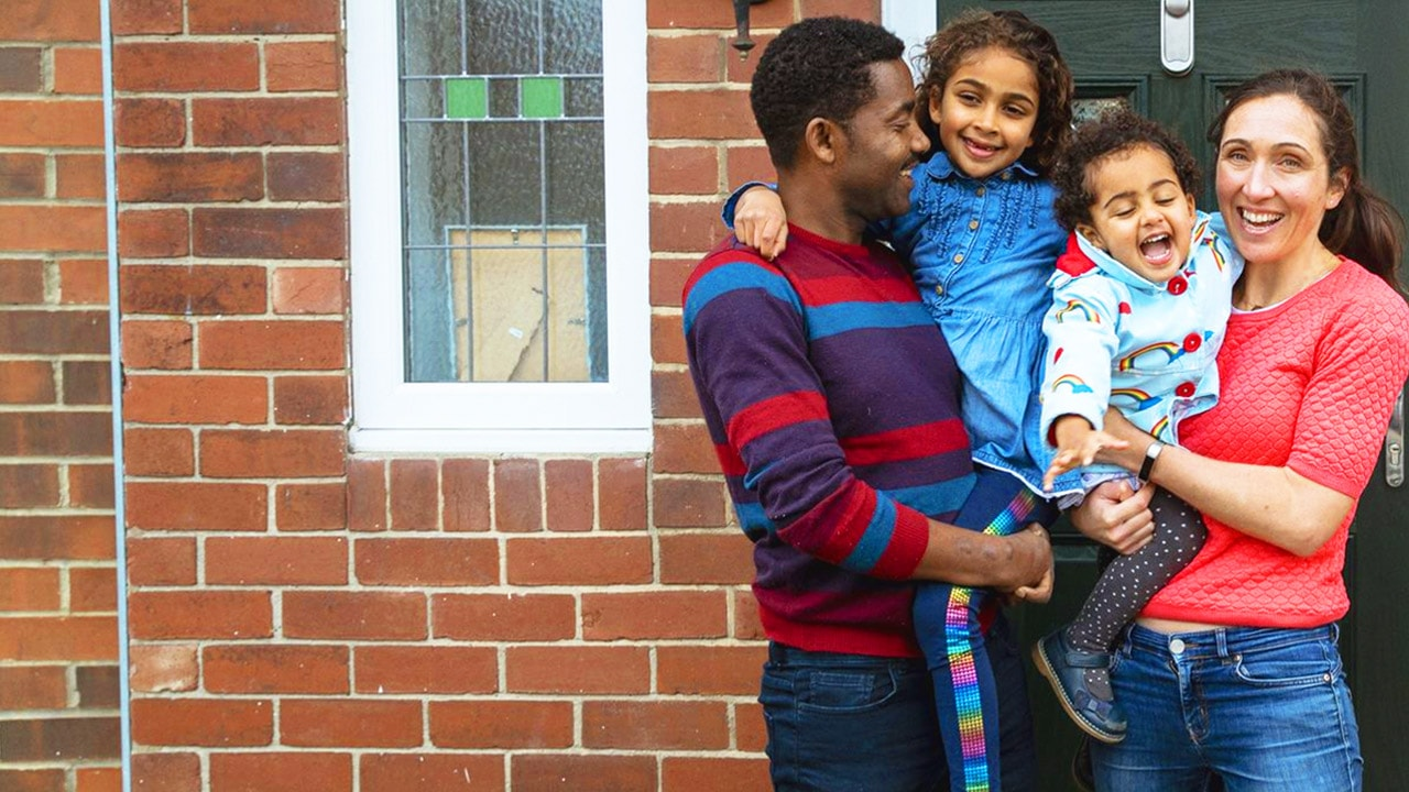 Young family standing together children held up smiling on their front doorstep
