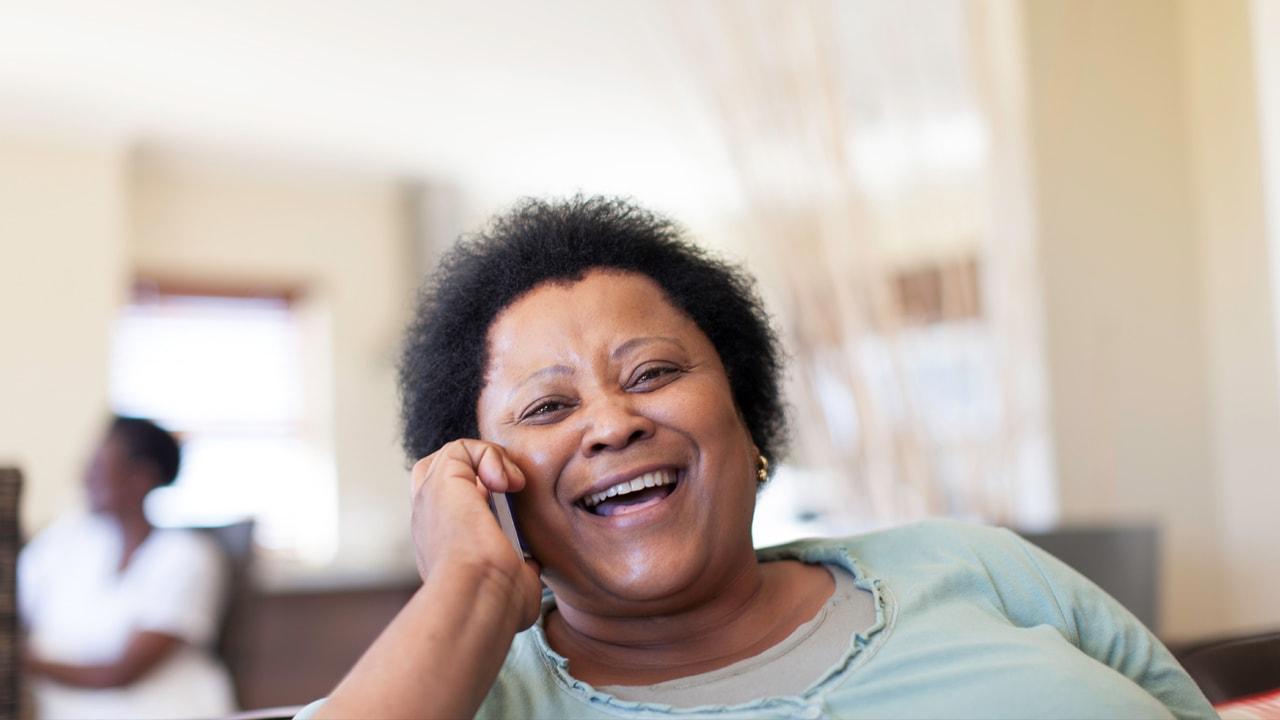 Woman sat smiling using mobile phone