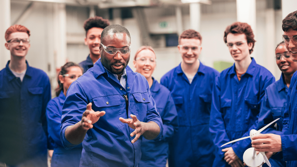 Group of young people learning at an engineering class wearing overalls and safety glasses