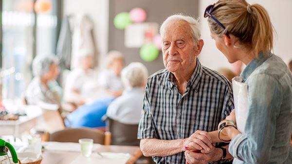 Woman giving reassuring hand to older man. In background older people are crowded together.