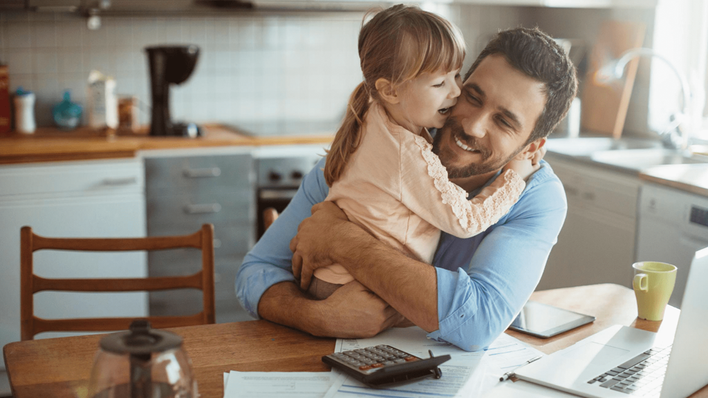 Young child and man hugging and laughing at kitchen table with calculator paperwork and laptop
