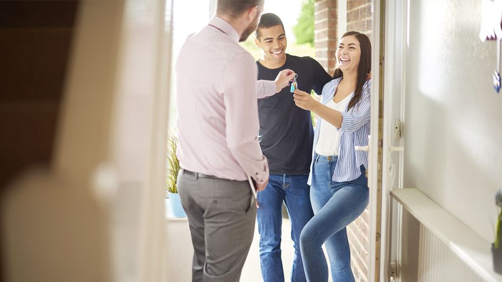 Man giving couple the keys to their new home