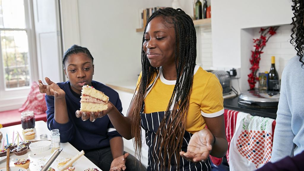 Cake in the kitchen, as two friends smile and admire their handywork