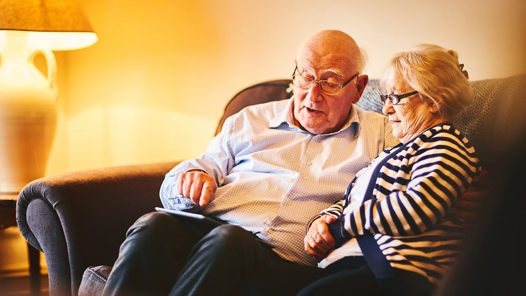 Older couple sat together on sofa looking at something on a mobile phone