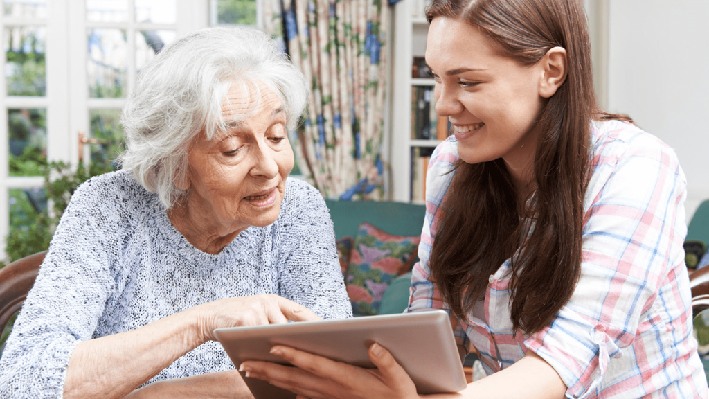 Older and younger woman sat at a table at home looking at an iPad tablet together