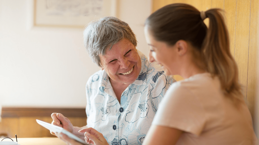 An older and younger woman sat together laughing and smiling looking at an iPad tablet