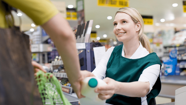 Cashier serving a customer in a supermarket shop