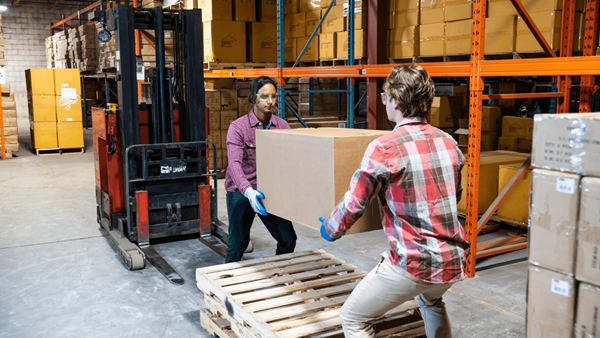 Two people lifting a large box in a warehouse