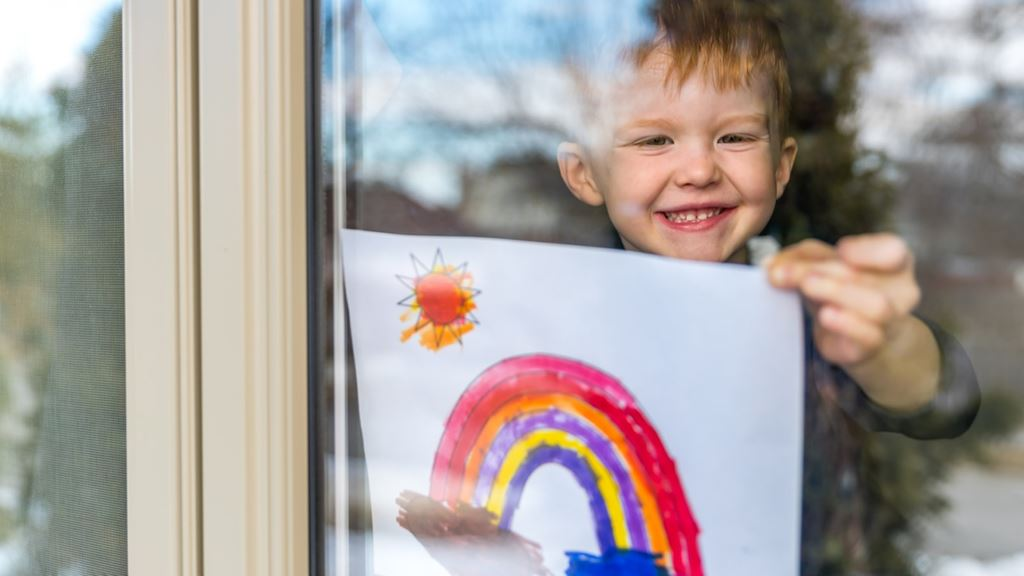 Young smiling child tapes a crayon drawing of a rainbow to the inside of a window.