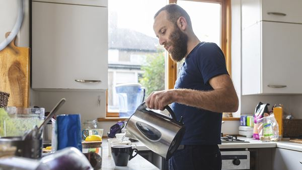 Man pours water from kettle in his kitchen