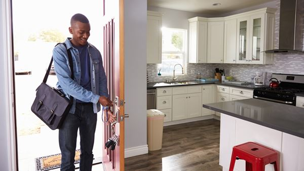 Young man smiling opens the door into a kitchen