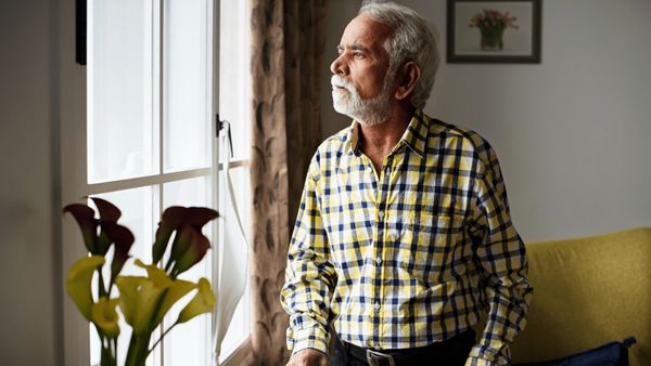 Older man with walking stick looks out of the lounge window