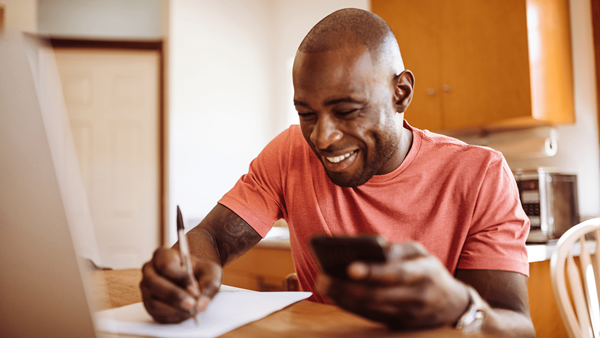 Man at kitchen table smiling and writing whilst looking at his phone