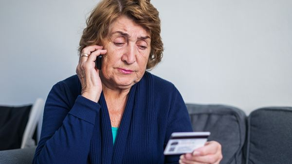 Older woman on mobile phone holding a credit card ready to make a payment