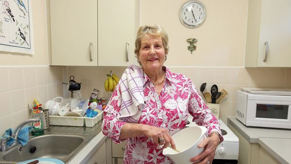 Florence in her kitchen holding a mixing bowel, behind her is an oven, to the left a sink and draining board, to the right a microwave. Resident.