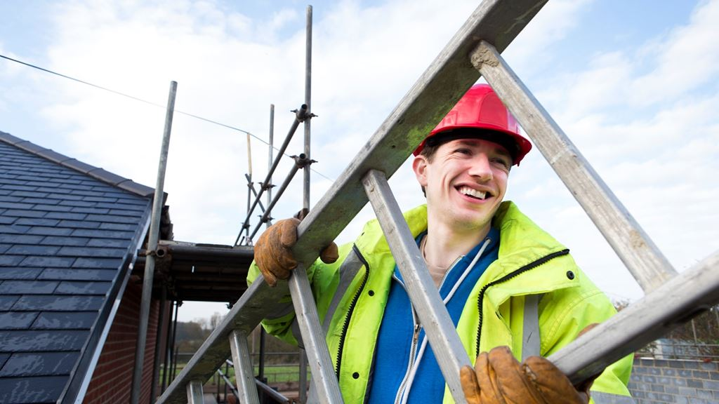 Man in hard hat and high-vis smiling carrying ladder, scaffolding next to house in the background, all part of our home improvement work