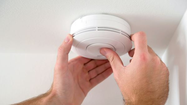 Closeup of hands testing a smoke or CO2 alarm on a ceiling for safety